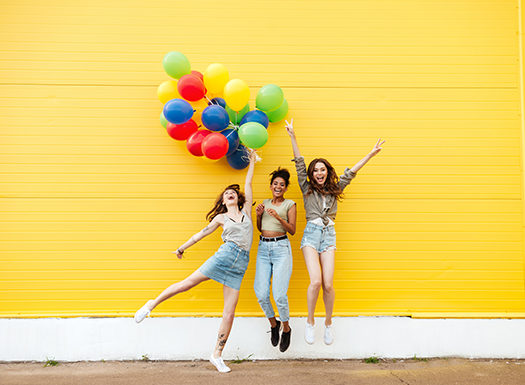 Girls holding balloons and jumping